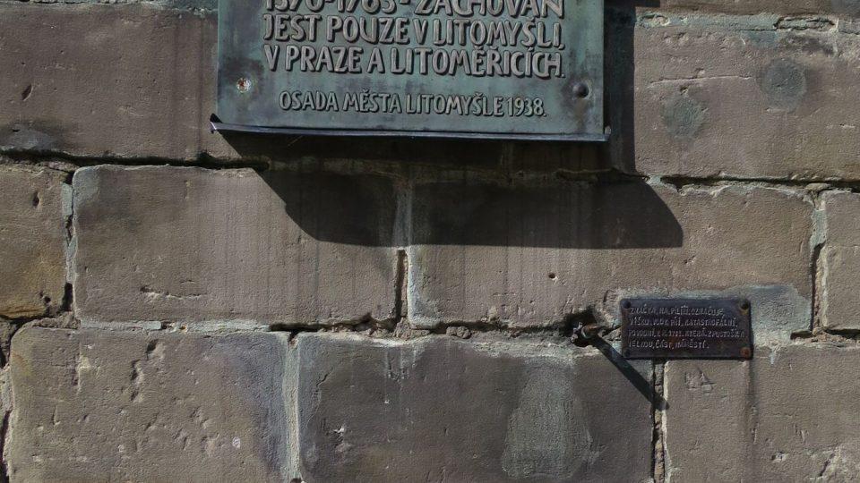 Bronzová deska nad zazděným českým loktem ve zdi radniční věže