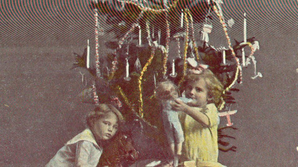 """Barevná vánoční pohlednice z 1. pol. 20. stol. - barevná (kolorovaná) fotografie dvou děvčátek u stromečku s dárky, stříbrný nápis """"Veselé vánoce!"""", dat. 1917."""