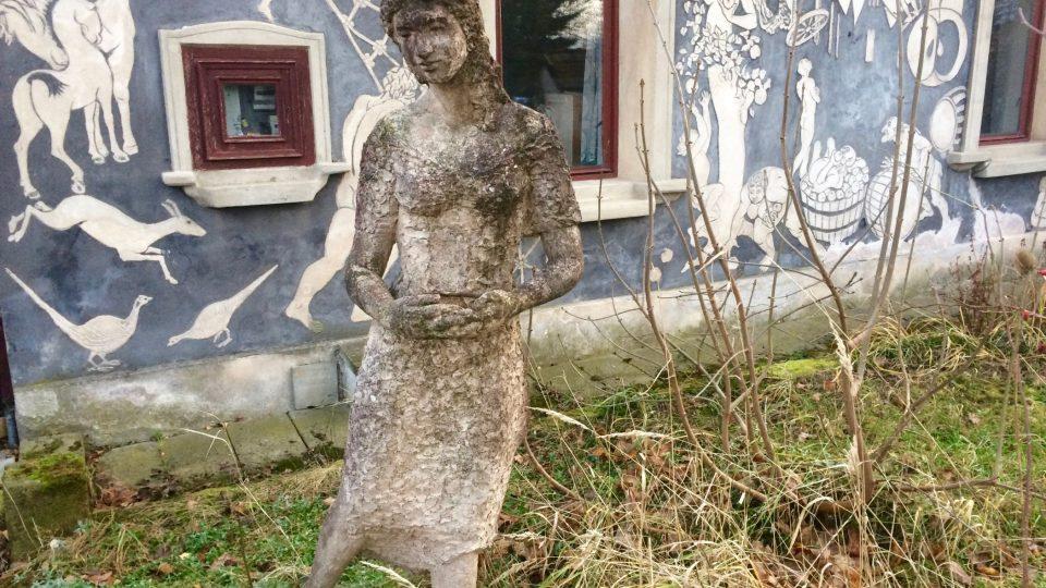 Dům i jeho okolí je také plné soch, tohle je tzv. vítací dívka u vchodu do domu z ulice