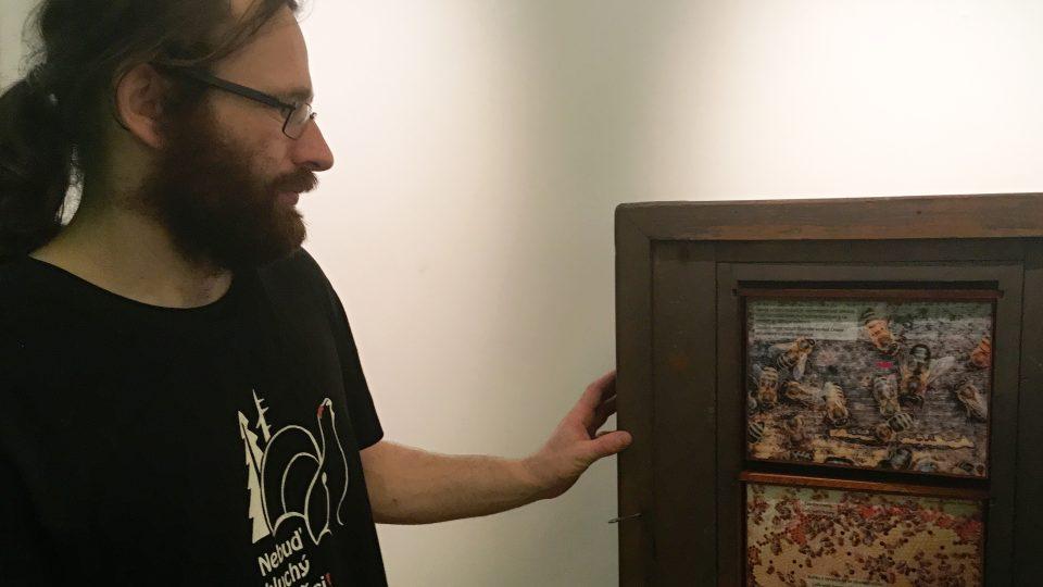 Kurátor Václav Beran u historického úlu s výjevy ze života včel