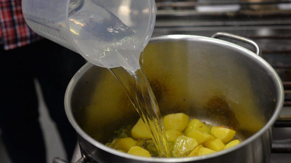 Po orestování se přidají brambory nakrájené na větší kostky a opět restujeme. Díky přítomnosti škrobu začnou brambory karamelizovat a hnědnout na povrchu. Až se tak stane, zalijeme je vývarem (nebo vodou)