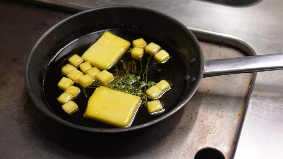 Na pánvi konfitujeme (vaříme v ponořeném stavu) na kachním sádle brambory