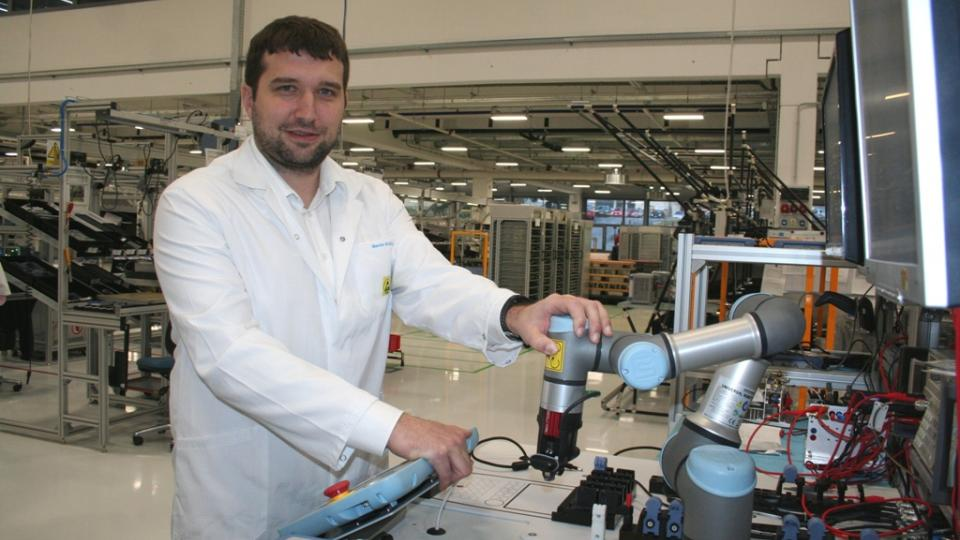 Martin Kudrle ukazuje, jak robotická ruka pomáhá ve firmě Rohde & Schwarz při testování elektronických měřicích přístrojů