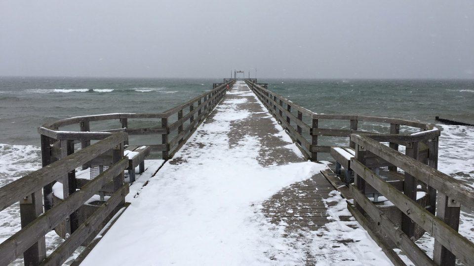 Je březen, na pláži leží sníh a od moře docela silně fouká