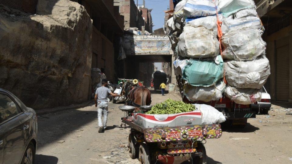 Úzkými prašnými uličkami se tlačí pick-upy i oslí povozy, všechny jsou naložené pytli s odpadky