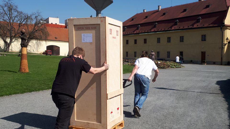 Stěhování sochy v transportní bedně do zámku