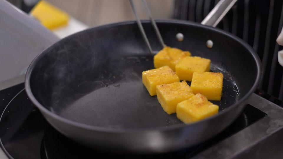 Polentu nařežeme na kostky a na pánvi opečeme na másle dozlatova