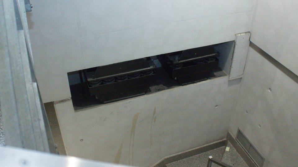 Černé ocelové bloky s pružinami tlumí otřesy od projíždějících vlaků a metra z podzemí