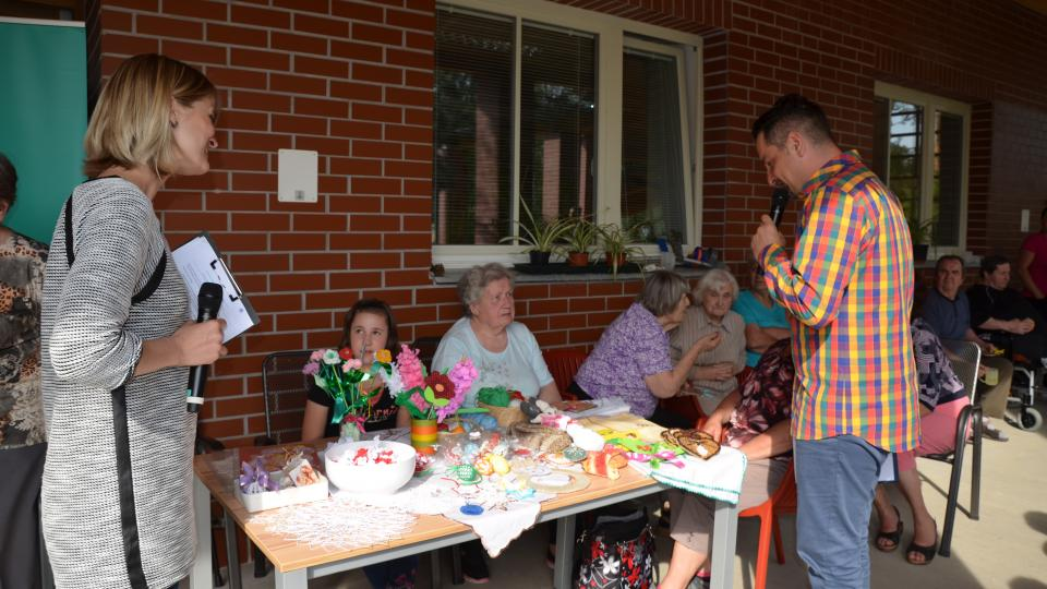 Veronika Albrechtová a Honza Macoun obdivují ruční práce seniorů