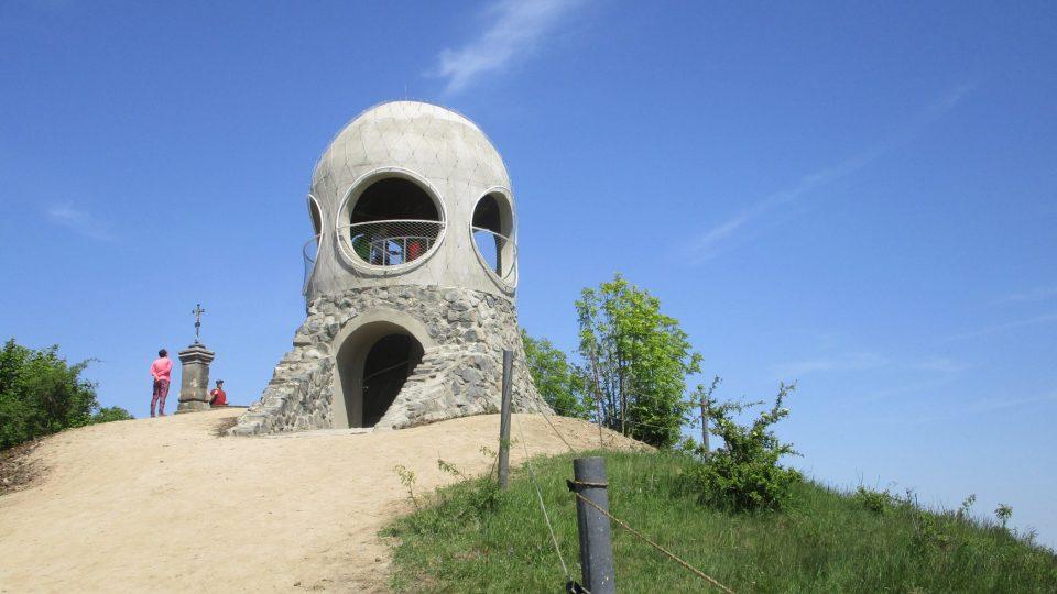 Netypická betonová rozhledna s kruhovými průzory příchozím turistům často připomíná styl Jana Kaplického
