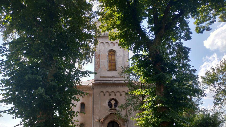 Zhlavní silnice není evangelický kostel skoro vidět. Zakrývají ho vzrostlé stromy