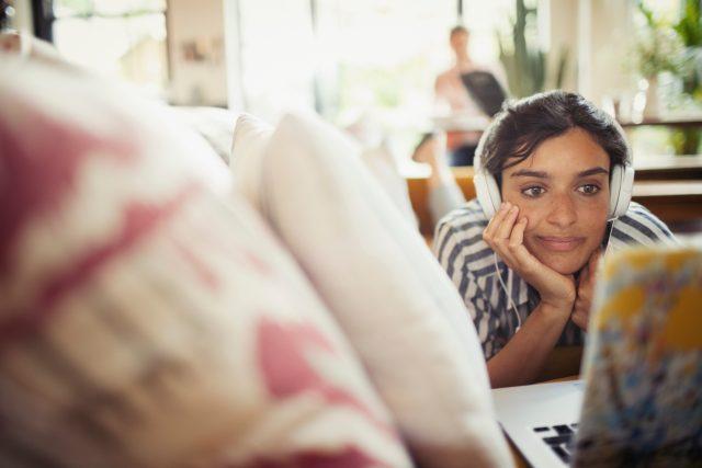 Mladá žena, notebook, online, sluchátka, gauč, sofa, obývák (ilustrační foto)