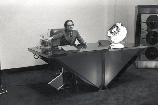 Pierre Cardin sedící za stolem svého vlastního designu
