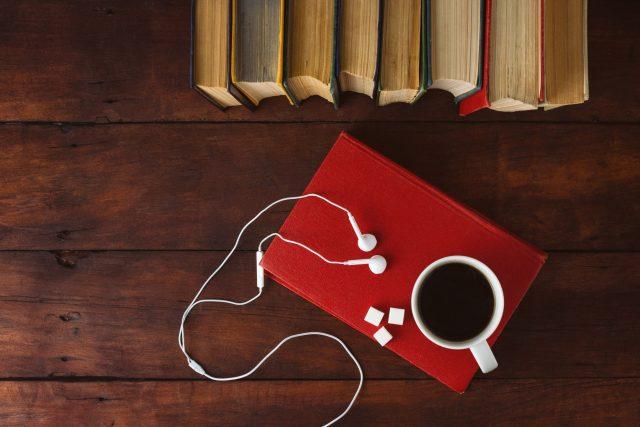 Knihy, bílá sluchátka, kostky cukru, šálek kávy