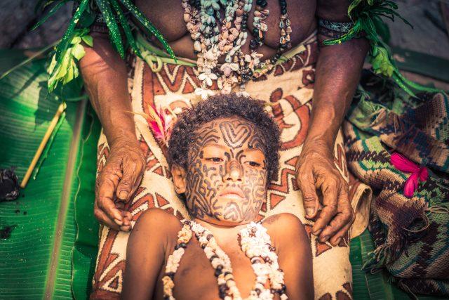 Papua Nová Guinea. S tetováním se zde začíná již v útlém věku. Fotograf zachytil moment, kdy je tetována malá dívka