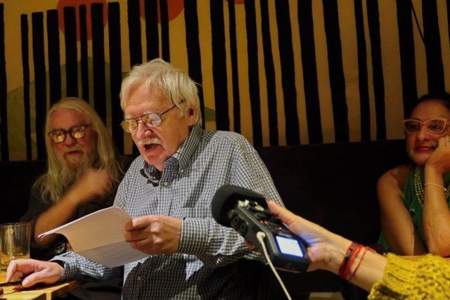Jiří Kratochvil čte fejeton. V pozadí Jan Zuziak a Monika Rychlíková